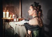 stock photo of mirror  - Beautiful young woman in green medieval dress sitting near mirror - JPG
