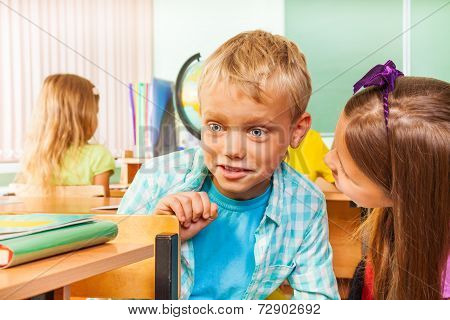 Amazed boy with big eyes sits on chair at desk