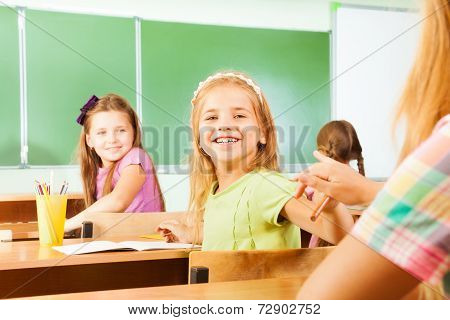 Desk row with smiling girls turned and looking