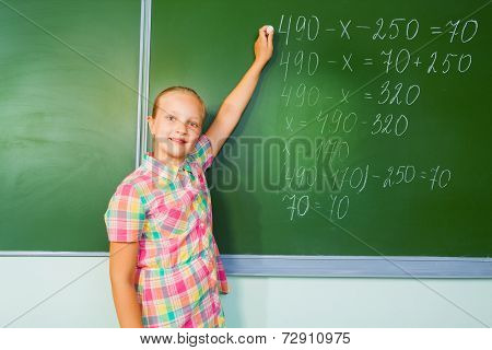 Girl with chalk writing mathematics equation