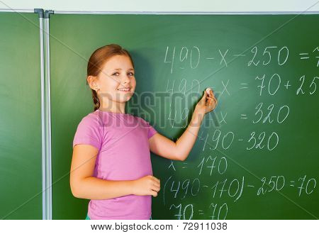 Beautiful girl with chalk in hand writes  equation