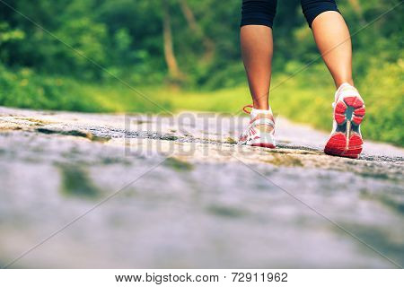 y oung fitness woman legs walking on forest trail