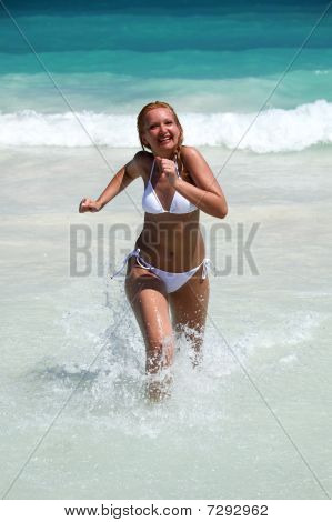 Young Woman Running Out Of Ocean