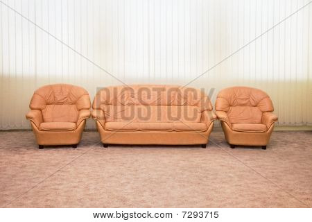 Leather Armchairs And Sofa In Interior Of Modern Room