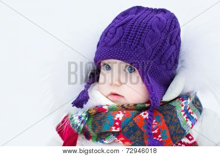 Cute Baby Girl Wearing A Warm Winter Hat And A Colorful Scarf On A Walk In A Winter Park