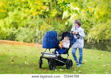 Happy Boy With His Little Siblings, A Cute Curly Toddler Girl And A Newborn Baby In Double Stroller
