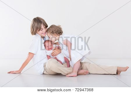 Three Beautiful Children Playing Together In A White Studio Wearing White Clothes