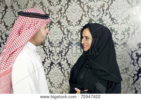 Arabian businessman talking with a woman wearing hijab