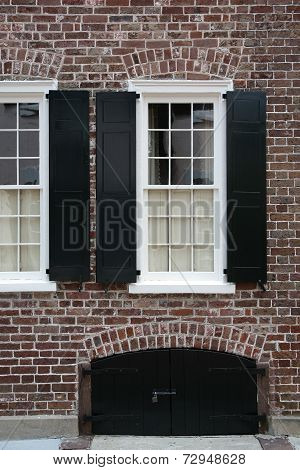Black shutters on red brick wall