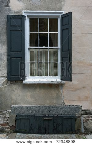 Black shutters on brown stone wall