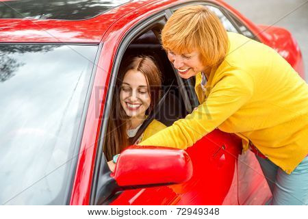 Mother with her daughter near red car