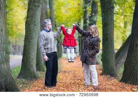 Happy Family Playing With A Little Toddler Girl In An Autumn Park