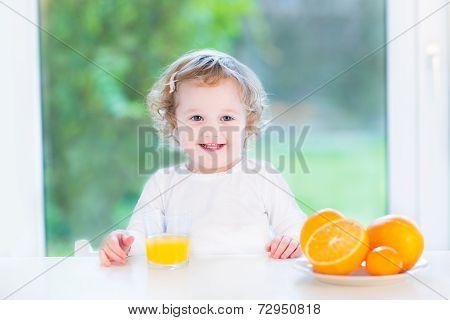 Smiling Happy Toddler Girl Having Orange Juice For Breakfast
