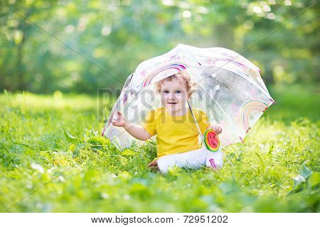 Happy Laughing Baby Girl Playing Under A Colorful Umbrella In A Summer Rain