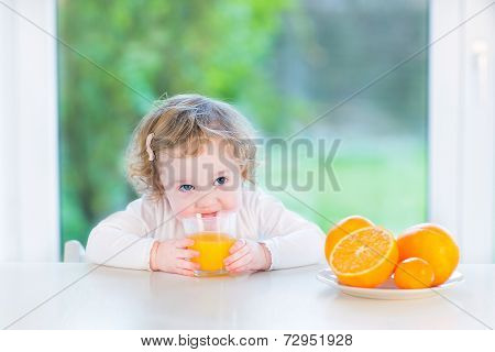 Cute Little Toddler Girl Drinking Orange Juice Sitting At A White Table Next To A Big Window