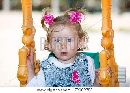 Happy Adorable Child Girl On Swing On Playground Near Kindergarten Montessori On Summer Day