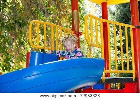 Happy Adorable Girl On Children's Slide On Playground Near Kindergarten Montessori On Summer Day