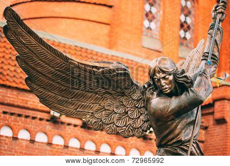 Statue Of Archangel Michael With Outstretched Wings Before Catholic Church