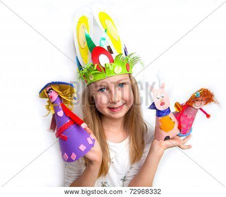 Little girl demonstrating her cruft work Easter bonnet, paper dolls and reindeer