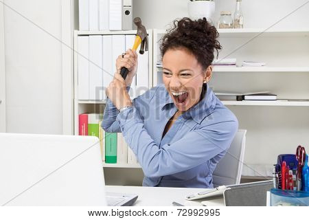 Overwhelmed woman with hammer at workplace