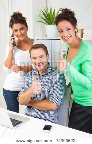 Three people showing thumbs up in office - happy teamwork