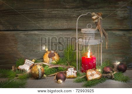 Rustic lantern with with red candle. Wooden christmas background with decoration.