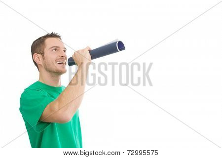 Young handsome man using a magazine as a speaking-tube