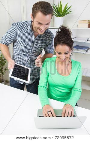 Smiling young man and woman working together in office