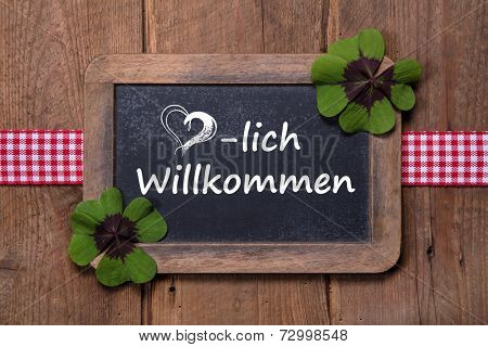 Old menu board with welcome message in german - clovers and ribbon on wooden background