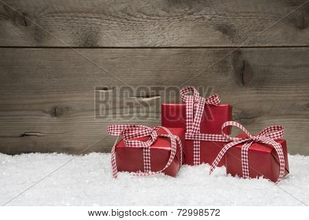 Three red gifts for christmas on a wooden background with snow for a greeting card