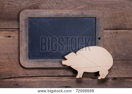 Menu board with pink pig on wooden background for New Year, sylvester, birthday or for a butcher - to say good luck