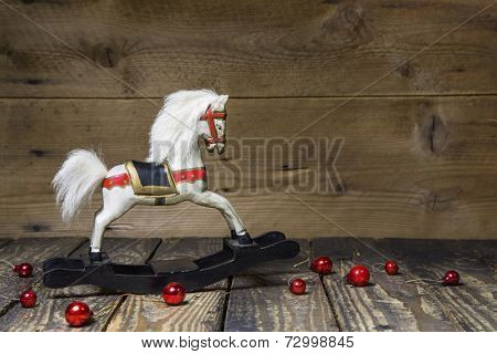 Vintage - old wooden rocking horse on a wooden old board for a christmas card with red balls - classic decoration