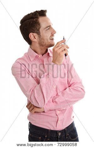Successful attractive young man in pink looking sideways holding pen isolated on white background