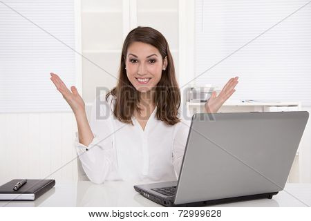 Dream job: successful smiling businesswoman sitting at desk with laptop and arms up