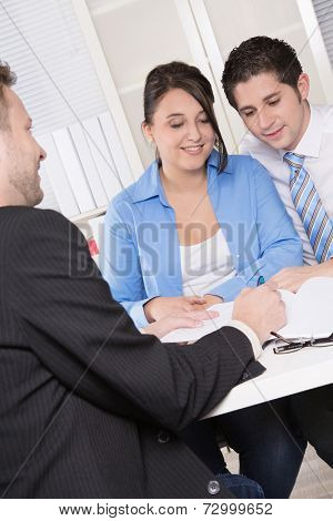 Happy couple discussing future financial plans with consultant at office