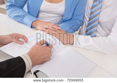 Terms and conditions of contract: close up of hands signing documents or paper