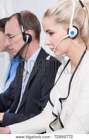 Profile of telesales or helpdesk team concentrating with headsets