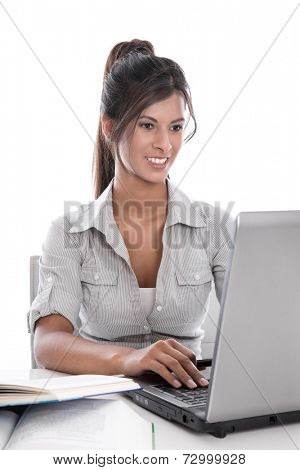 Young pretty smiling businesswoman sitting at desk with computer at work in the office - talking with friends at web cam.