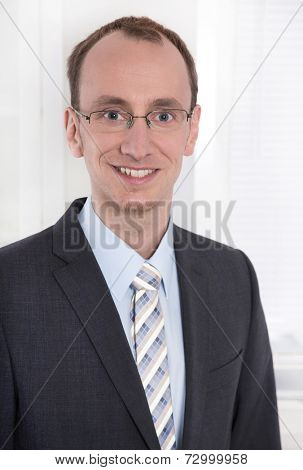 Portrait of a young smiling businessman or engineer with glasses in suit and tie