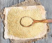 stock photo of millet  - Millet on a wooden table with a spoon - JPG