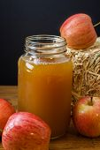 picture of cider apples  - Fresh pressed apple cider and apples on a wooden table with a hay bale in the background - JPG