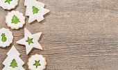image of linzer  - Overhead view of green jam filled Christmas Linzer cookies decorated with icing sugar and aranged as a border on a wooden background - JPG
