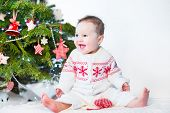 picture of christmas baby  - Funny Laughing Baby Girl Playing Under A Red And White Decorated Christmas Tree Wearing A Knitted Jacket - JPG