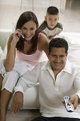 image of mobile-phone  - Family sitting on sofa watching TV mother on mobile phone - JPG