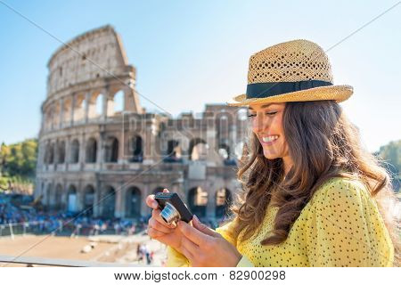 Happy Young Woman Checking Photos In Camera In Front Of Colosseu
