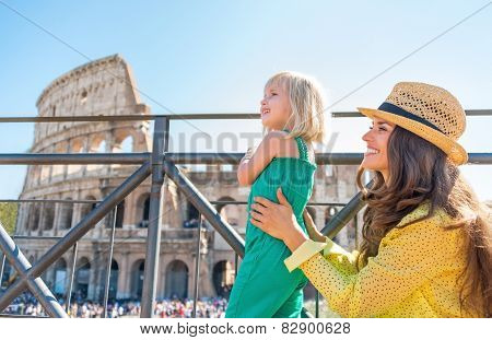 Mother And Baby Girl Looking On Copy Space In Front Of Colosseum