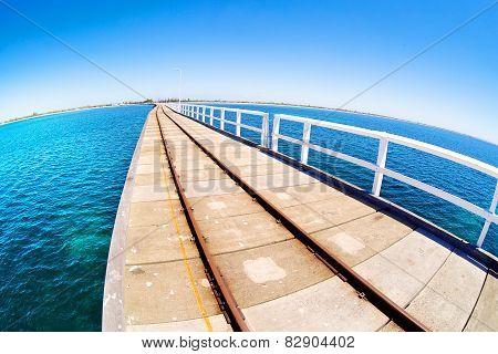 Pier in blue ocean water with fisheye horison. Basselton jetty