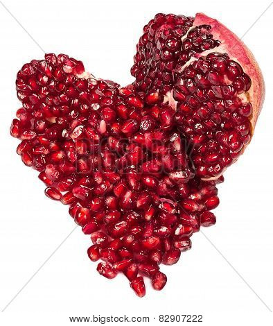 Pomegranate And Seeds In A Heart-shaped  Isolated On A White
