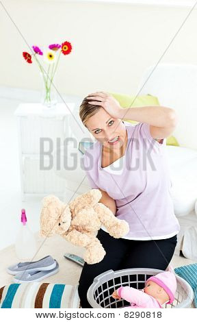 Blond Young Woman With Headache Putting Toys Into A Basket