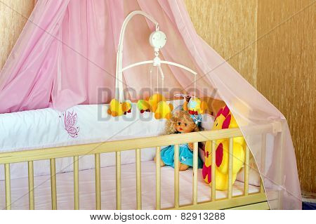 Various Soft Toys In The Cot With Orange Linen